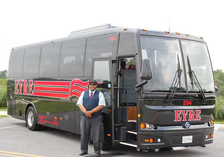 Eyre shuttle bus driver in front of 30 passenger coach.